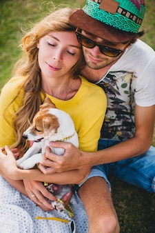 Junges stilvolles hipster-paar in der liebe, die auf gras sitzt und hundewelpe jack russell im tropischen strand spielt, weißer sand, cooles outfit, romantische stimmung, spaß, sonnig, mann frau zusammen, urlaub