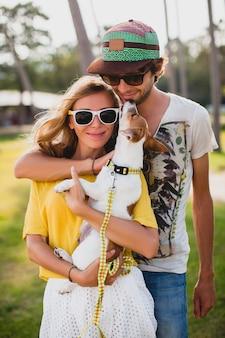 Junges stilvolles hipster-paar in der liebe, die einen hund am tropischen park hält, lächelt und spaß während ihres urlaubs hat, sonnenbrille, mütze, gelbes und bedrucktes hemd, romantik tragend