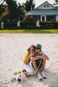 Junges stilvolles hipster-paar in der liebe, die mit hund im tropischen strand geht und spielt