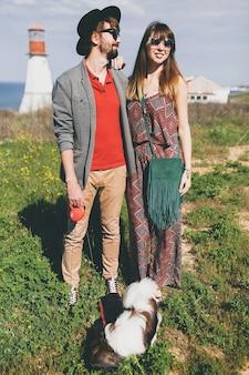 Junges stilvolles hipster-paar in der liebe, die mit hund in der landschaft geht