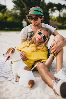 Junges stilvolles hipster-paar in der liebe zu fuß spielen hund welpe jack russell, tropischer strand, cooles outfit, romantische stimmung, spaß haben, sonnig, mann frau zusammen, horizontal, urlaub, haus zu hause villa