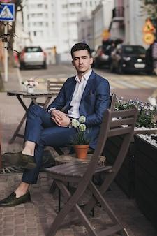 Junges stilvolles hübsches geschäftsmannmodell im anzug, der in der straße sitzt. high fashion look