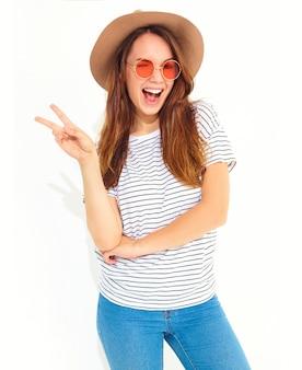 Junges stilvolles lachendes frauenmodell im zufälligen sommer kleidet im braunen hut mit dem natürlichen make-up, das auf weißer wand lokalisiert wird. friedenszeichen blinzeln und zeigend