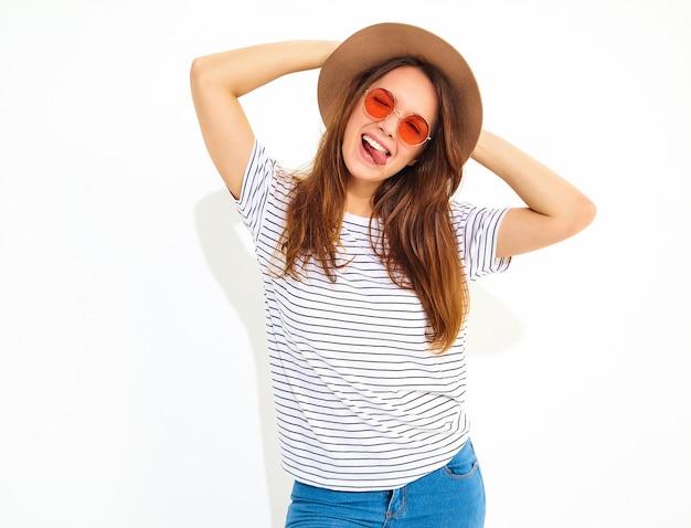 Junges stilvolles lachendes frauenmodell im zufälligen sommer kleidet im braunen hut mit dem natürlichen make-up, das auf weißer wand lokalisiert wird.