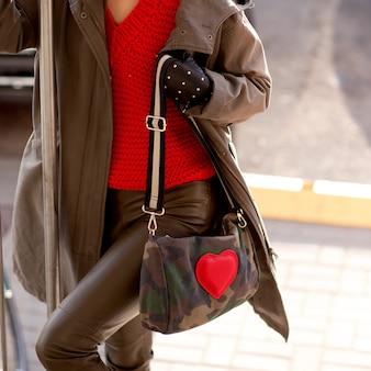 Junges stilvolles mädchen in den lederhosen, in einer roten strickjacke und in den händen einer hellen tasche