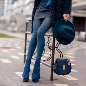 Junges stilvolles mädchen in der blauen mantel- und kleidungsaufstellung