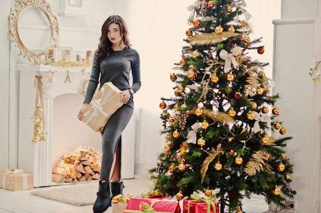 Junges stilvolles mädchen mit weihnachtsgeschenken und dekoration des neuen jahres