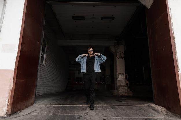 Junges stilvolles mannmodell in einer modischen blauen jeansjacke in schwarzen hosen in turnschuhen in sonnenbrille kommt aus dem dunklen raum. attraktiver hipster-typ geht die straße in der nähe des gebäudes entlang.