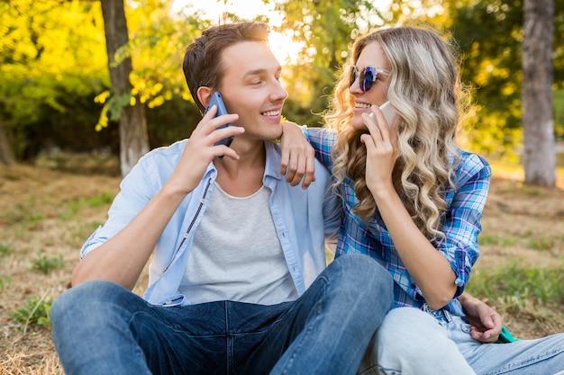 Junges stilvolles paar, das im park sitzt, glückliche familie des lächelnden mannes und der frau zusammen spricht am telefon