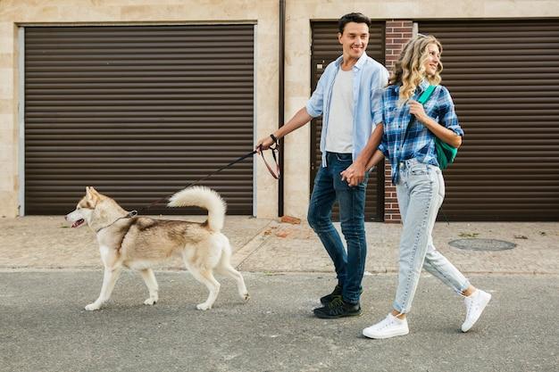 Junges stilvolles paar, das mit hund in straße geht. mann und frau glücklich zusammen mit husky rasse