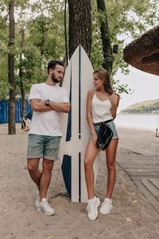 Junges stilvolles paar, das t-shirts und shorts trägt, die draußen im park nahe surfbrett gehen