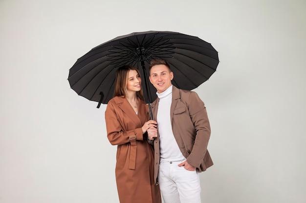 Junges stilvolles paar mit schwarzem regenschirm zeigt liebesgefühle. porträt von süßen emotionalen menschen in herbstkleidung, die unter einem regenschirm stehen, während sie auf hellgrauem hintergrund schauen. platz für website kopieren