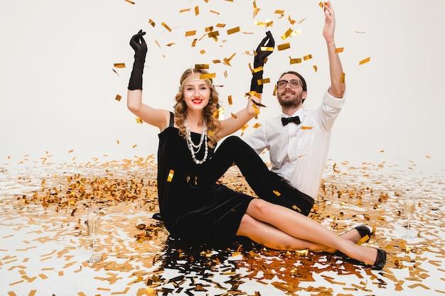 Junges stilvolles paar verliebt, auf boden sitzend, goldenes konfetti werfend