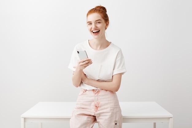 Junges stilvolles rothaariges mädchen, das handy verwendet, während mit jemandem gesprochen und lächelt
