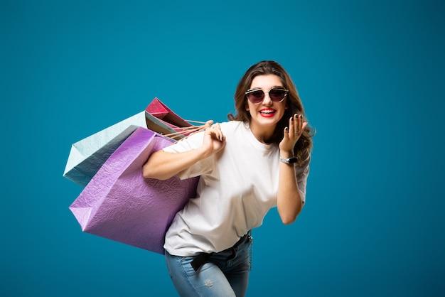 Junges stilvolles schönes mädchen in der sonnenbrille geht mit bunten einkaufstaschen spazieren