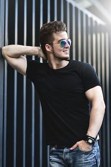 Junges stilvolles und selbstbewusstes glückliches hübsches kerlmodell im t-shirt-lebensstil in der straße in der sonnenbrille