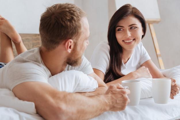 Junges strahlendes paar, das sich beim trinken aromatischen kaffees auf schlechtem niveau entspannt und über positiven moment der woche spricht