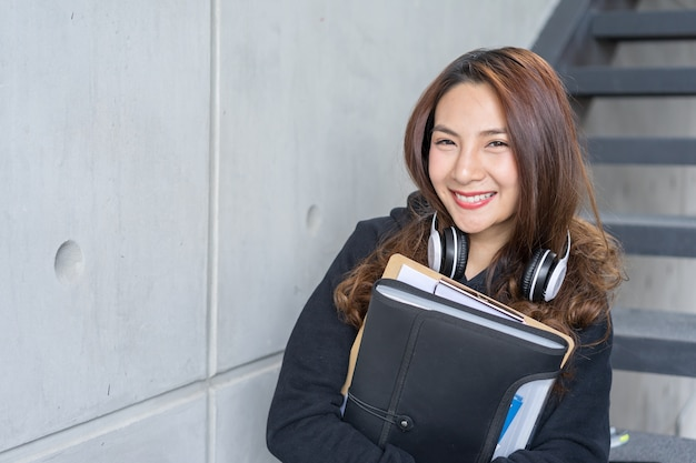 Junges studentenfrau sitzen auf treppe mit dem ordner und kopierbuch und kopfhörer im campus
