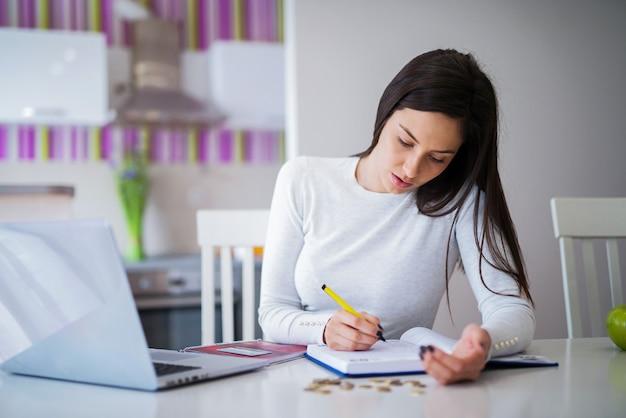 Junges studentenmädchen, das an ihrem schreibtisch sitzt und notizen macht.