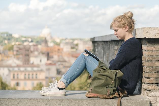 Junges studentenmädchen, das ein elektronisches buch im park liest