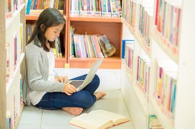 Junges studentenmädchen, das in einer bibliothek sitzt