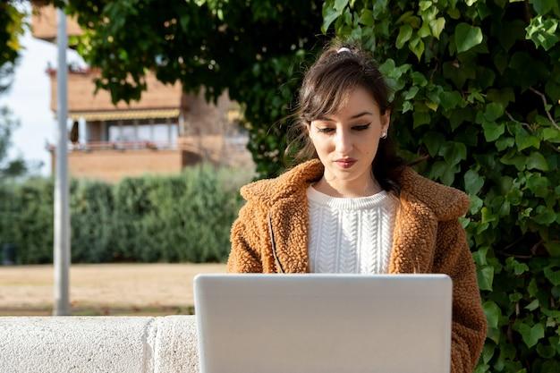 Junges studentenmädchen, das mit ihrem laptop am park arbeitet.
