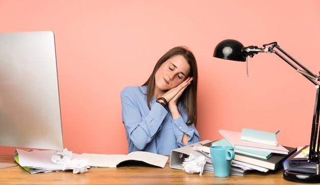 Junges studentenmädchen, das schlafgeste im entzückenden ausdruck macht