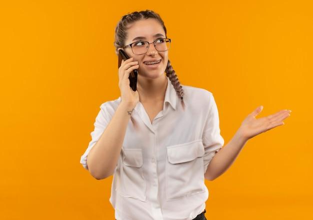 Junges studentenmädchen in den gläsern mit zöpfen im weißen hemd, das auf dem handy lächelnd zeigt und mit dem arm zur seite steht, die über orange wand steht