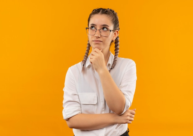 Junges studentenmädchen in den gläsern mit zöpfen im weißen hemd, das beiseite mit hand auf kinn mit nachdenklichem ausdruck auf gesicht denkt, das über orange wand steht