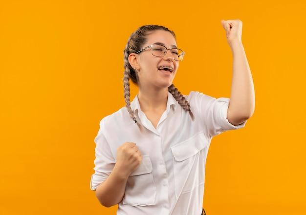 Junges studentenmädchen in den gläsern mit zöpfen im weißen hemd, das die fäuste glücklich und aufgeregt ballt, die ihren erfolg freuen, der über orange hintergrund steht