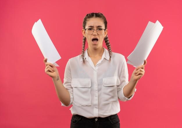 Junges studentenmädchen in den gläsern mit zöpfen im weißen hemd, das leere seiten hält, die nach vorne schauen, enttäuscht von den erhobenen armen, die über rosa wand stehen
