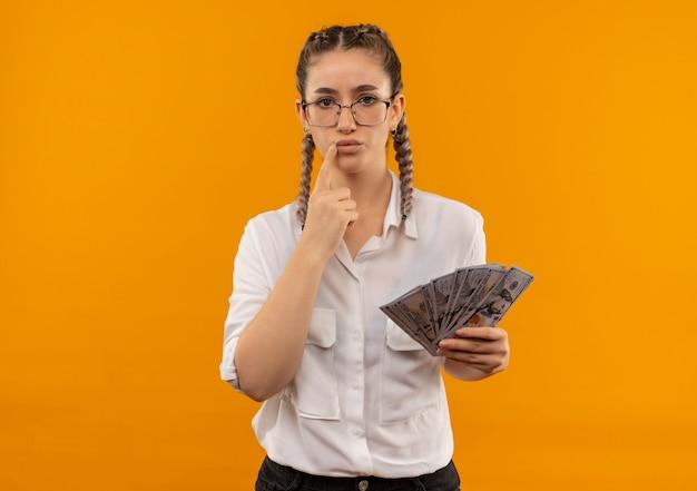 Junges studentenmädchen in gläsern mit zöpfen im weißen hemd, das bargeld hält, das nach vorne mit nachdenklichem ausdruck denkt, der zweifel hat, die über orange wand stehen