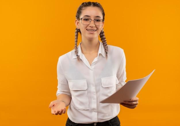 Junges studentenmädchen in gläsern mit zöpfen im weißen hemd, das leere seiten hält, die nach vorne lächelnd fröhlich über orange wand stehen