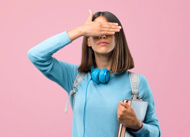 Junges studentenmädchen mit blauer strickjacke und kopfhörern, die augen abdecken. zurück zur schule