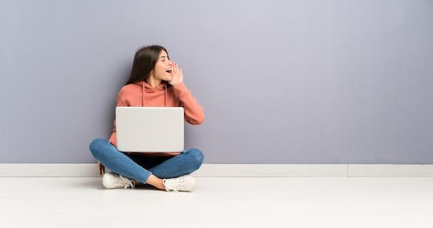 Junges studentenmädchen mit einem laptop auf dem boden, der mit dem breiten mund schreit, öffnen sich