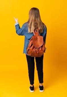 Junges studentenmädchen über gelber wand