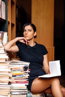 Junges studentenmädchen, welches das buch sitzt auf dem haufen von büchern an der alten bibliothek liest