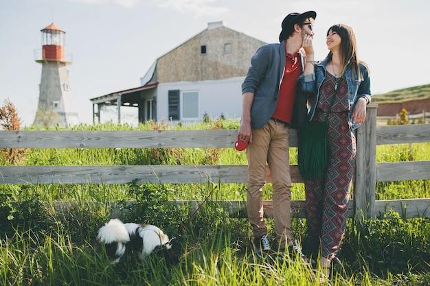 Junges stylisches hipster-paar in der liebe, das mit hund auf dem land spazieren geht