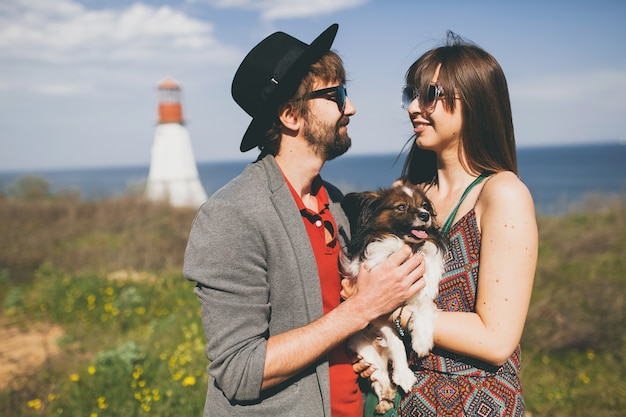 Junges stylisches hipster-paar in der liebe, das mit hund auf dem land spazieren geht Kostenlose Fotos