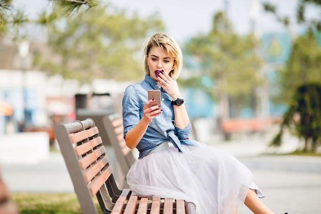Junges süßes blondes mädchen mit kurzen haaren, die auf einer holzbank sitzen, schaut auf smartphone und wird schockiert, ihren mund mit der hand schließend