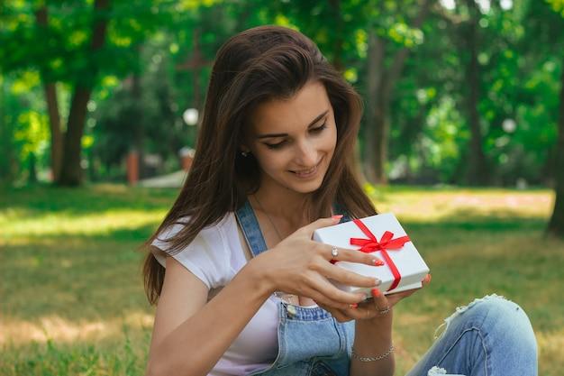 Junges süßes jugendlich, das im park sitzt und ein geschenk öffnet
