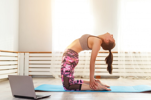 Junges süßes mädchen praktiziert yoga zu hause, nimmt posen ein und schaut auf einen laptop