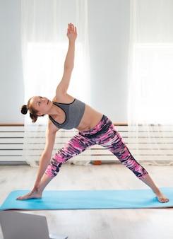 Junges süßes mädchen praktiziert yoga zu hause, nimmt posen ein und schaut auf einen laptop.