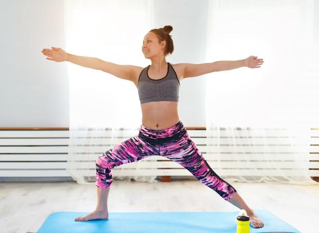 Junges süßes mädchen praktiziert yoga zu hause und nimmt posen ein