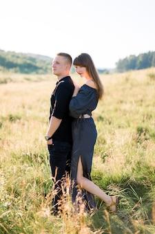 Junges süßes paar verliebt, stilvolle schwarze kleidung tragend, im freien auf der sommerwiese posierend