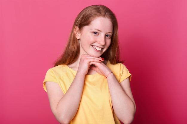 Junges süßes süßes mädchen mit lächeln auf ihrem gesicht, arme nahe kinn haltend. rothaarige dame mit roter maniküre stellt auf rosa lokalisiert auf. menschen- und emotionskonzept.