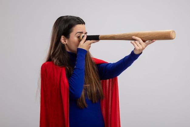 Junges superheldenmädchen, das blickgeste mit baseballschläger lokalisiert auf weiß zeigt