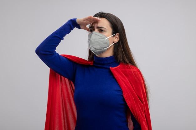 Junges superheldenmädchen, das medizinische maske trägt, die entfernung mit hand lokalisiert auf weiß betrachtet