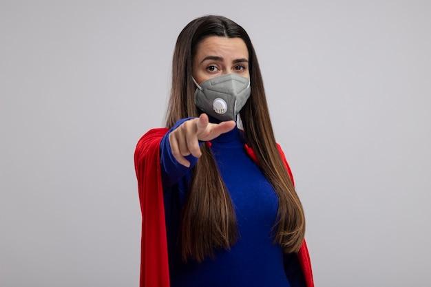 Junges superheldenmädchen, das medizinische maske trägt, die sie geste lokalisiert auf weißem hintergrund zeigt
