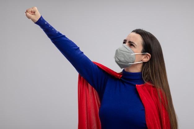 Junges superheldenmädchen, das medizinische maske trägt faust erhöht auf lokalem hintergrund